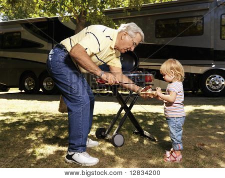Grandfather giving granddaughter hotdog by RV.