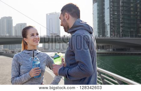 fitness, sport, people and lifestyle concept - smiling couple with bottles of water outdoors over dubai city street background