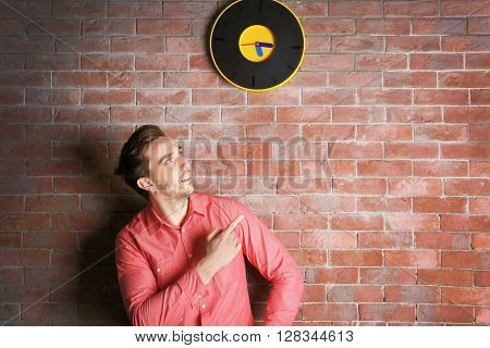 Man in a pink shirt standing beside a  big clock on a brick wall