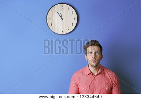 Man in a pink shirt standing beside a  big clock on blue wall