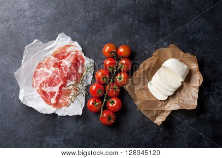 Prosciutto, mozzarella and cherry tomato over stone table. Top view