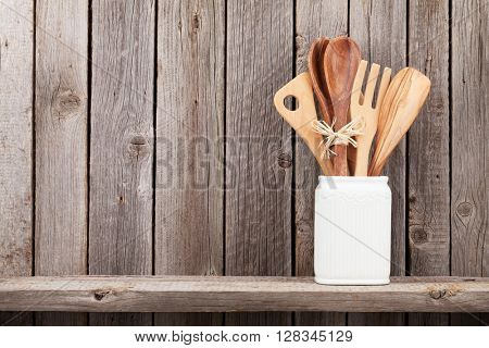 Kitchen utensils on shelf against rustic wooden wall