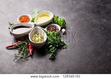 Herbs, condiments and spices on stone background. View with copy space