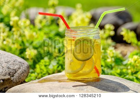 Lemonade with lemon and lime shot on a bright sunny day.