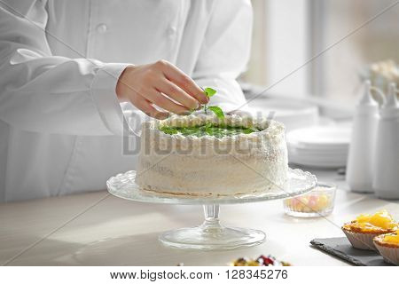 Female hands decorating cake with mint.