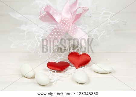 Candy favor, red hearts and sugared almonds on blue-gray wooden background