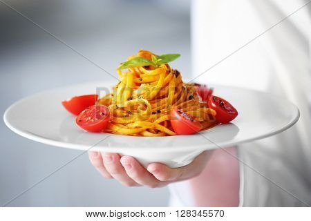 Chef hand holding delicious cold pasta salad in bowl on the table closeup