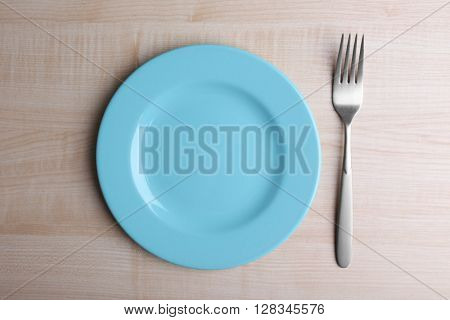 Empty plate with silver fork and knife on wooden background