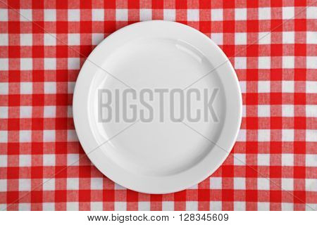 Empty plate on red checkered background