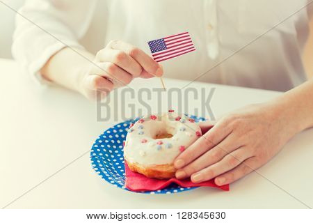 american independence day, celebration, patriotism and holidays concept - close up of female hands decorating glazed donut with american flag decoration on disposable plate at 4th july party from top