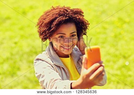 technology, communication and people concept - happy african woman taking selfie with smartphone at summer park