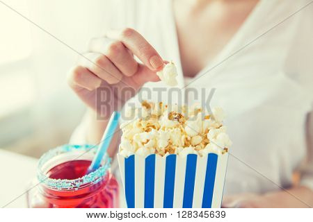 american independence day, celebration, patriotism and holidays concept - close up of woman eating popcorn with drink in glass mason jar at 4th july party