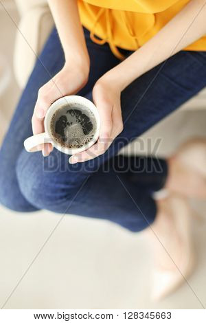 Woman holding cup of coffee at home