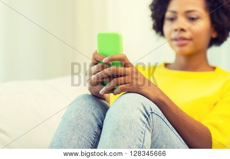 people, technology and leisure concept - close up of happy african american young woman texting on smartphone at home