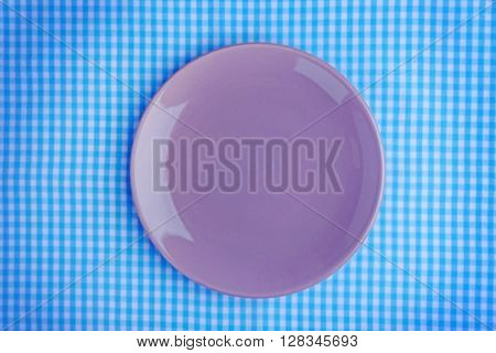 Empty plate on checkered fabric background