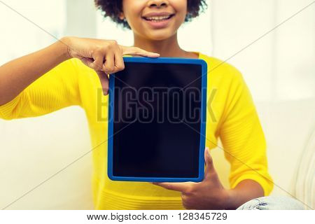 people, technology, advertisement and leisure concept - close up of happy african american young woman sitting on sofa and showing tablet pc computer black blank screen at home