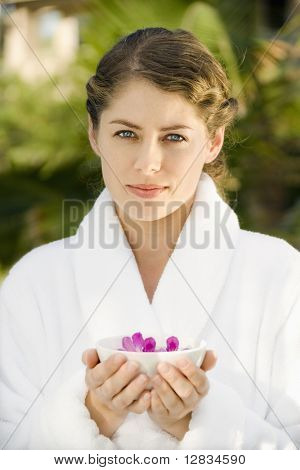 Attractive Caucasian mid-adult woman in white robe holding bowl of purple orchids floating in water.