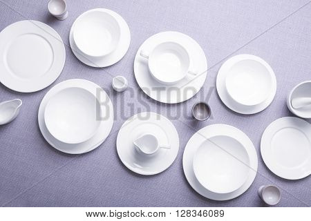 Empty white dishes on grey background.