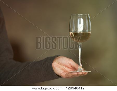 Man holding white wine in a glass, close up