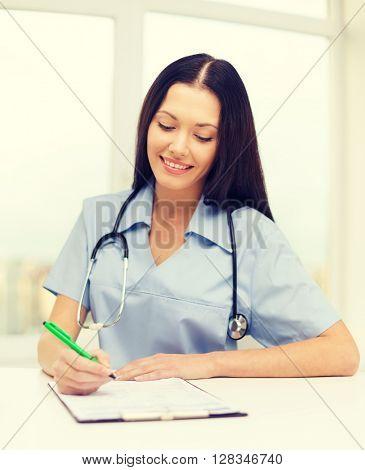 medicine and health concept - female doctor or nurse writing prescription