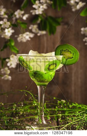 kiwi fruit soft drink cocktail with ice on a wooden background with flowers.