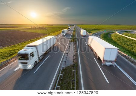 Many delivery trucks driving through agricultural fields. Fast blurred motion drive on the freeway in beautiful spring scenery. Freight scene on the motorway near Belgrade Serbia.