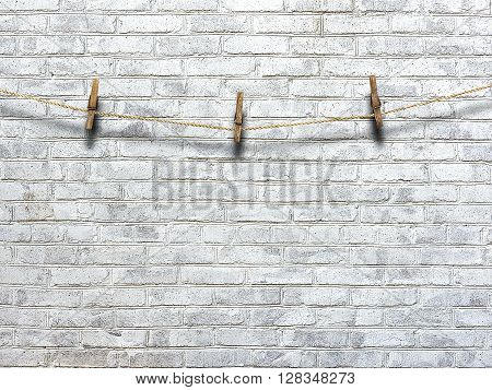 clothesline with clothespins on a background of a brick wall