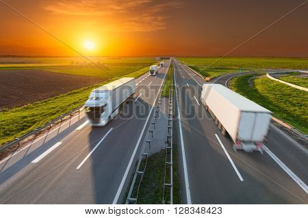 Many white trucks driving towards the sun. Fast blurred motion drive on the freeway at beautiful sunset. Freight scene on the motorway near Belgrade Serbia.