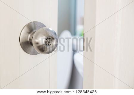 Close-up stainless door knob, with door open slightly