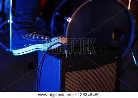 Musician's foot stepped on amplifier, close up