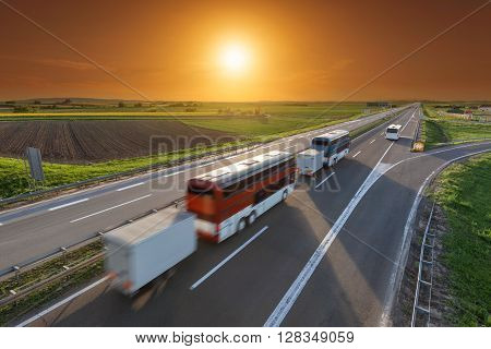 Colorful buses driving in blurred motion on the freeway at beautiful sunset. Transport and travel scene on the motorway near Belgrade Serbia.