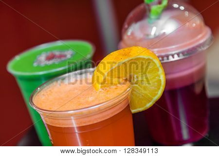 Strawberry, raspberry, orange, kiwi and avocado smoothies in plastic recyclable cups