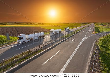 Three white gasoline tanker trucks in line driving towards the sun. Fast gasoline delivery on the freeway at beautiful sunset. Freight scene on the motorway near Belgrade Serbia.
