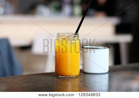 Homemade sea buckthorn lemonade in jar and cup of tea with shallow depth of field