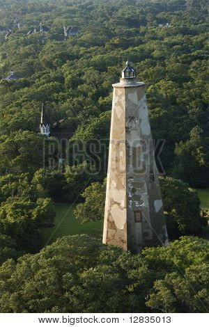 Aerial view of Old Baldy lighthouse in wooded park at Bald Head Island, North Carolina.