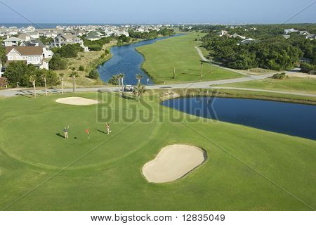 Aerial view of two people palying golf near residential community at Bald Head Island, North Carolina.