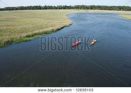 Aerial of two teenage boys kayaking through marshland on Bald Head Island, North Carolina.