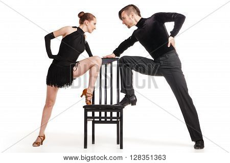 Beautiful two professional artists dancing with chair over white background