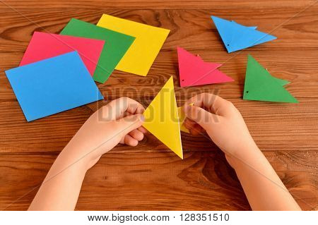 Origami colorful fish, paper sheets. Child holds an yellow origami fish in his hands. Kids crafts idea. Brown wooden table