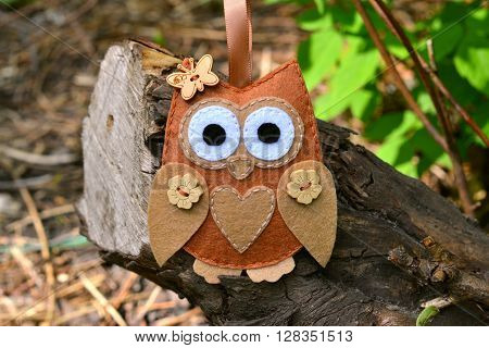Felt owl toy on a branch. Felt soft bird toy outdoor, kids crafts. DIY concept