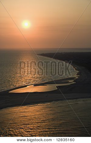 Aerial view of sun over Atlantic ocean and shoreline of Bald Head Island, North Carolina.