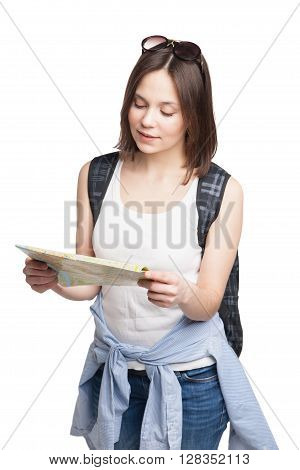 young pretty girl in looking for place on  map with rucksack over white background