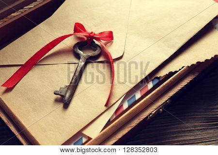 Old key with envelopes on wooden table closeup