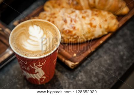 Freshly baked almond croissant and a take away cup of cappucchino on a table in a restaurant