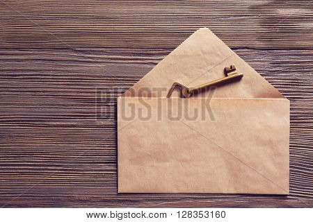 Old key with envelope on wooden background