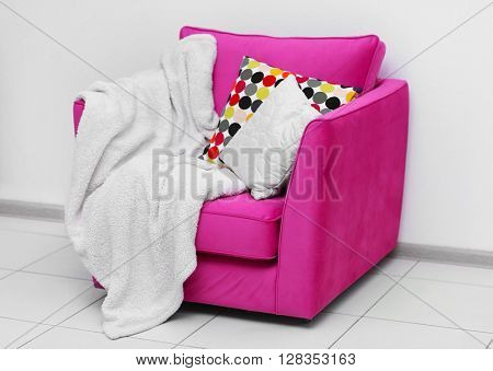 Pink armchair with blanket and pillows on light wall background