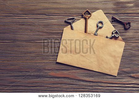 Group of old keys with envelope on wooden background