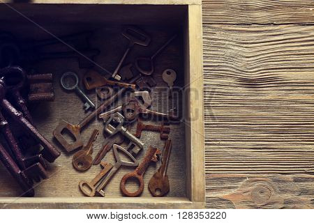 Wooden box full of old keys, top view