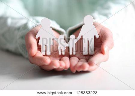Female hands holding white family figures