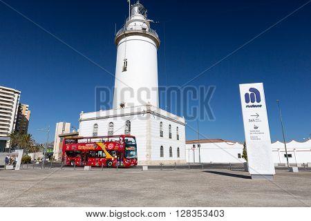 MALAGA, SPAIN - SEPTEMBER 4 2014: White lighthouse and turistic bus near Marina